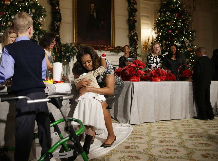 U.S. first lady Michelle Obama hugs a girl at the State Dining Room of the White House during an event to preview the 2013 holiday decorations December 4, 2013 in Washington, DC. The first lady hosted military families for the first viewing of the decorations and demonstrating holiday crafts and treats to military children. Photo: Alex Wong, Getty Images