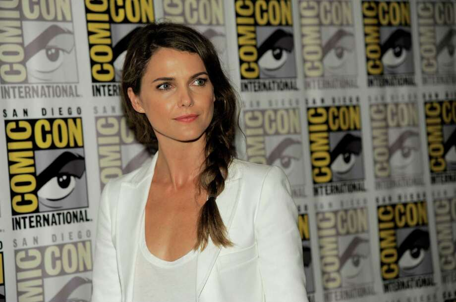 """FILE - In a  Saturday, July 20, 2013 photo, Keri Russell attends the """"Dawn of the Planet of the Apes"""" press line on Day 4 of  Comic-Con International in San Diego, Calif. New York City police say thieves broke into Keri Russell's Brooklyn home early Wednesday, Dec. 4, 2013 while the actress was sleeping and stole a laptop, jewelry and a purse. (Photo by Chris Pizzello/Invision/AP, File) ORG XMIT: NY126 Photo: Chris Pizzello / Invision"""