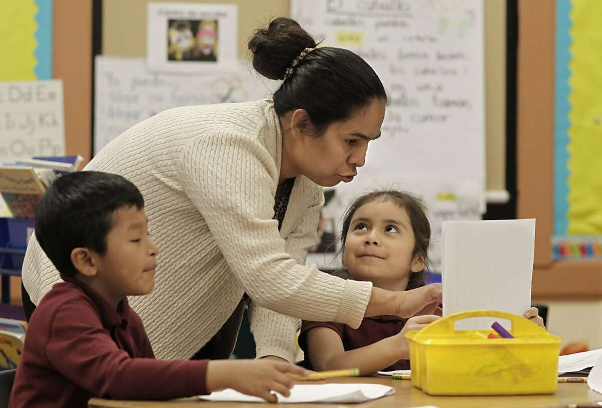 Parent and volunteer, Marta Hildalgo, on Wednesday Dec. 4, 2013, helps out students Alberto Mismis, (left) and Marta Lopez in a 1st grade bilingual class at John Muir elementary school, in San Francisco, Ca. A new study shows parents are less likely to be involved in their child's education if they are poor and the majority of parents overall know little about the way the state of California is funding education.