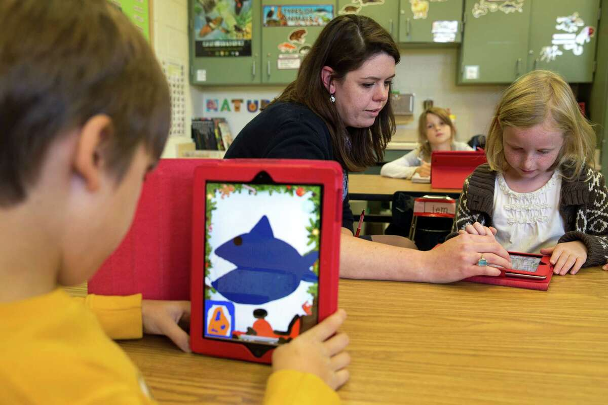 This photo taken Nov. 25, 2013 shows second grade teacher Heather Black working with Ingrid Soracco, 7, right, on her e-book assignment using an iPad at Jamestown Elementary School in Arlington, Va. Needed to keep a school building running these days: Water, electricity _ and broadband. Interactive digital learning on laptops and tablets is, in many cases, replacing traditional textbooks. Students are taking computer-based tests instead of fill-in-the bubble exams. Teachers are accessing far-off resources for lessons. (AP Photo/Jacquelyn Martin) ORG XMIT: WX203