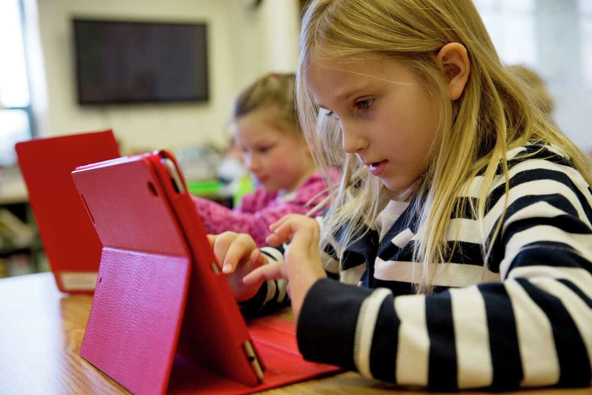 This photo taken Nov. 25, 2013 shows Ella Russell, 7, working on an e-book on an iPad during her second grade class at Jamestown Elementary School in Arlington, Va. Needed to keep a school building running these days: Water, electricity _ and broadband. Interactive digital learning on laptops and tablets is, in many cases, replacing traditional textbooks. Students are taking computer-based tests instead of fill-in-the bubble exams. Teachers are accessing far-off resources for lessons. (AP Photo/Jacquelyn Martin) ORG XMIT: WX202