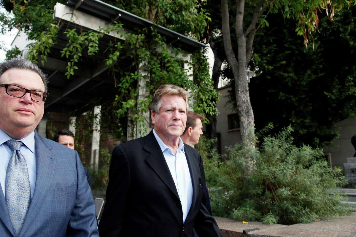 In this Monday, Dec. 2, 2013 file photo, actor Ryan O'Neal, right, leaves court after he testified in a Los Angeles courtroom about his relationship with Farrah Fawcett and his claimed ownership of an Andy Warhol portrait of the actress. A reality TV producer told a jury on Wednesday Dec. 4, 2013, that he believes O'Neal stole a Warhol portrait of Fawcett taken from the late actress' condominium. Craig Nevius provided photos and video that is being used by the University of Texas at Austin in its case against O'Neal to gain possession of the portrait, which the actor says was a gift from Warhol.