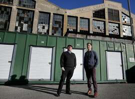 Patrick Keenan (right) and Steven Lucero stand among some old storage containers which will be replaced with modern shipping containers with windows for the popup events in San Francisco, Calif Tuesday December 3, 2013. SQFT is planning a development in a parking lot at 20th and Illinois Streets for next year that will include retail, restaurants, even a hotel and drive-in theatre all with shipping containers.