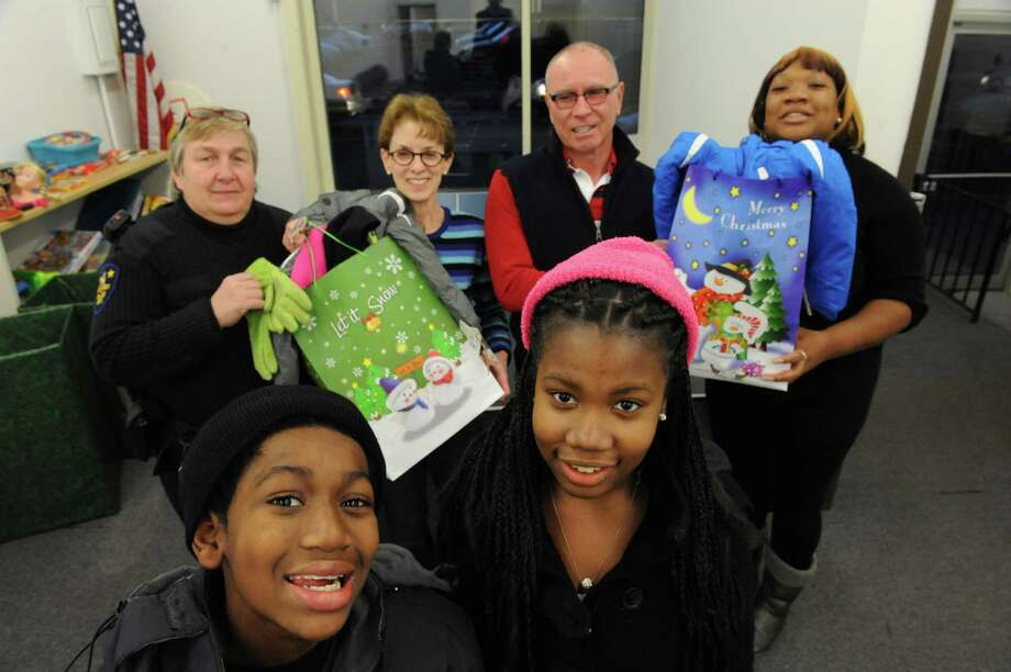 Jerry, 10, and Daijah, 13, Ford, front, police officer Colleen Goldston, left back, Lynn Kopka, Mark McGrath and Elvira Ford are collecting coats and mittens and gloves for the first time to start a winter clothing program through the Troy Central Little League on Wednesday Dec. 4, 2013 in Troy, N.Y. (Michael P. Farrell/Times Union) Photo: Michael P. Farrell / 00024889A