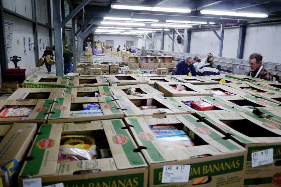Volunteers pack up food in the salvage room at the Regional Food Bank of Northeastern New York on Wednesday, Dec. 4, 2013 in Latham, NY.   (Paul Buckowski / Times Union) Photo: PAUL BUCKOWSKI / 00024886A