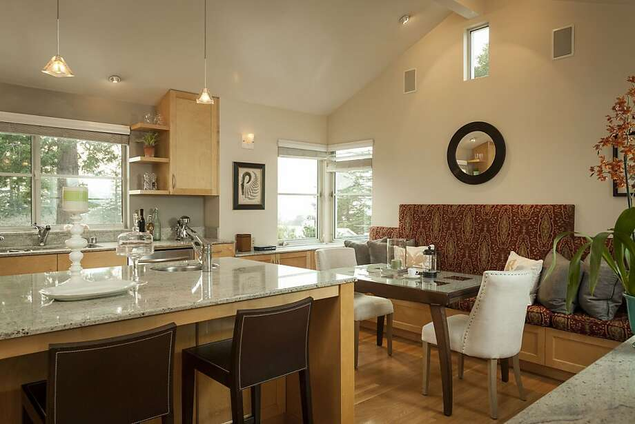The kitchen of 5423 Proctor Ave. in Oakland includes a built-in banquette and center island with breakfast bar. Photo: Scott Hargis Photography