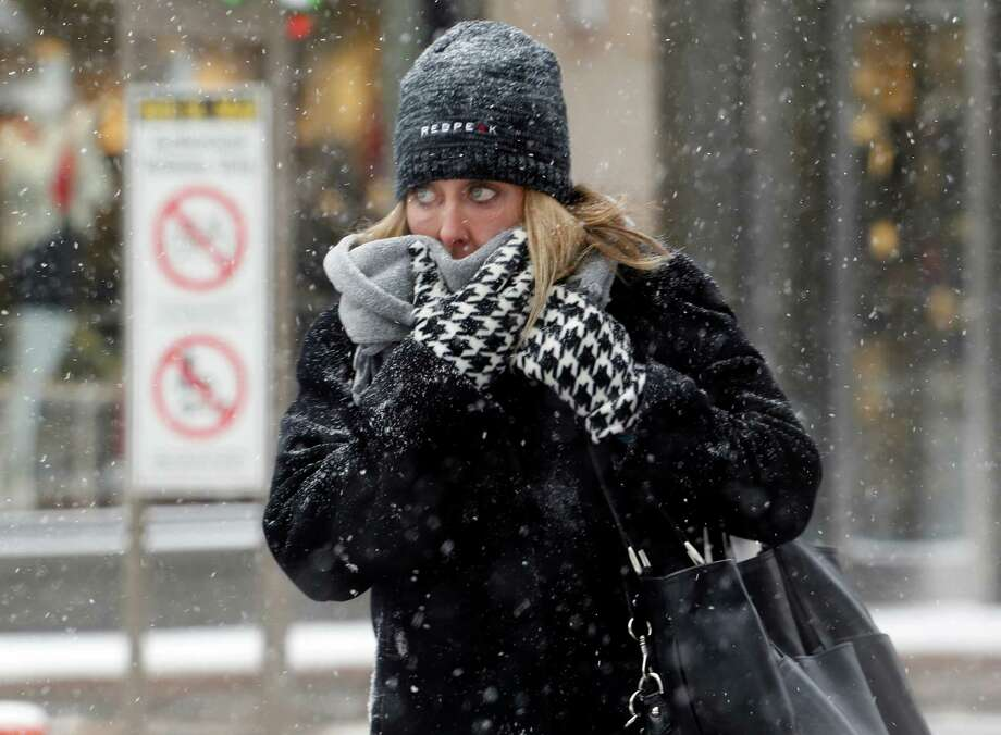 A woman braces against the cold and blowing snow on Denver's 16th Street Mall on Wednesday, Dec. 4, 2013. A wintry storm pushing through the Rockies and Midwest is bringing bitterly cold temperatures and treacherous driving conditions. (AP Photo/Ed Andrieski) ORG XMIT: COEA101 Photo: Ed Andrieski / AP