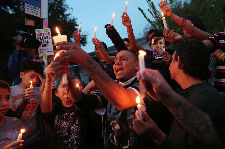 Along with family and friends, Leo Hernandez, center, yells out his 17-year-old daughter's name during a vigil for her at a bus stop at the 1100 block of Mission Road, Wednesday, Dec. 4, 2013. The girl was stabbed to death at the bus stop on Tuesday. Eduardo Reyes, 17, has been arrested and charged in her murder. A picture of Hernandez is seen behind the father. Photo: JERRY LARA, San Antonio Express-News / © 2013 San Antonio Express-News
