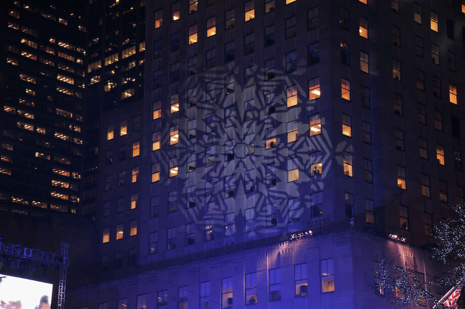NEW YORK, NY - DECEMBER 04:  A snowflake is projected onto the building prior to 81st Annual Rockefeller Center Christmas Tree Lighting Ceremony at Rockefeller Center on December 4, 2013 in New York City. Photo: Stephen Lovekin, Getty Images / Getty Images