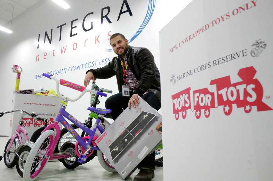 Marine GySgt. Albert Roman, Jr. (retired), poses with some of the toys collected for the Toys for Tots program at Integra Networks warehouse on Wednesday, Dec. 4, 2013 in Colonie, NY.  Roman who is a logistics coordinator at Integra Networks has taken over running the toy program after stepping away from it last year.  David Prescott, president and CEO of Integra, a Navy veteran, has donated money and allowed Roman and his fellow volunteers to use Integra's warehouse for the toys program.   (Paul Buckowski / Times Union) Photo: PAUL BUCKOWSKI / 00024904A