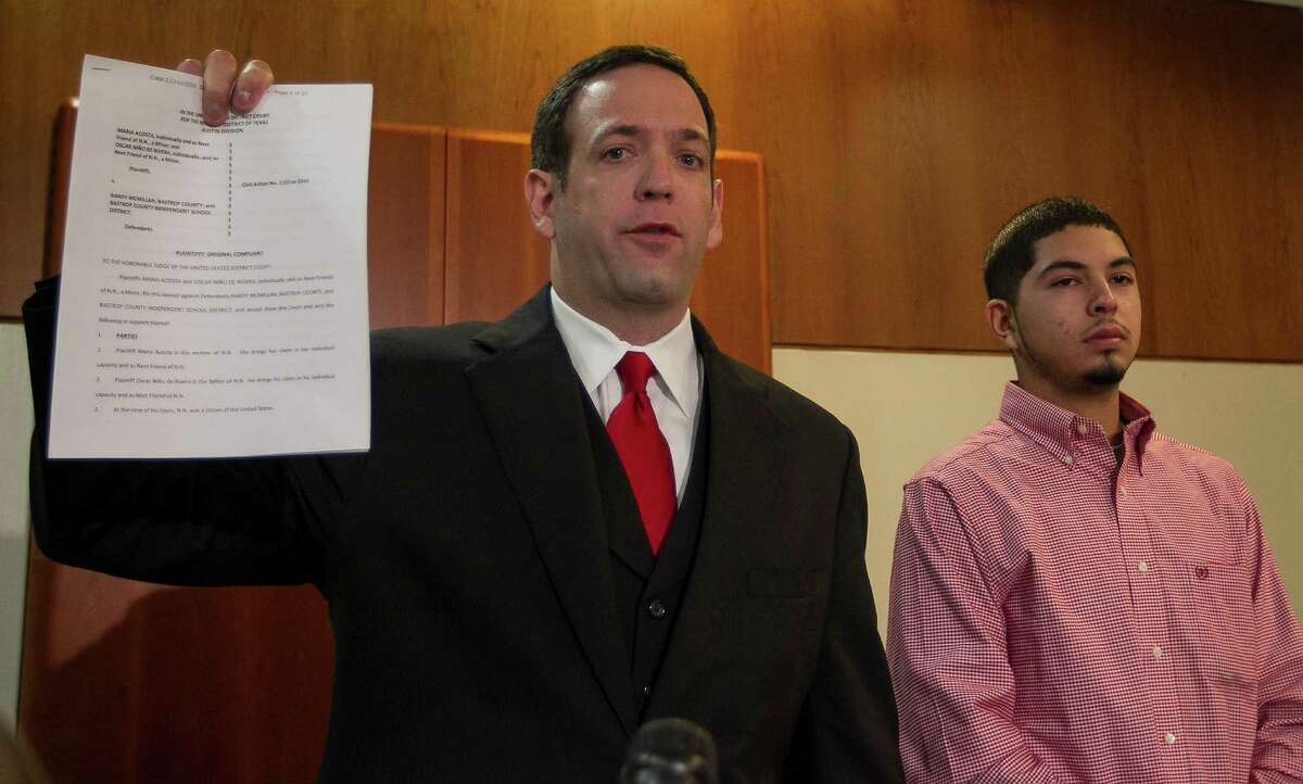 Attorney Adam Loewy, left, holds up a copy of the lawsuit he has filed for the family of Noe Nino de Rivera, 17, as Noe's brother Jesus Nino de Rivera, right, looks on during a press conference in Austin on Nov. 26. Nino de Rivera was critically injured when he fell and hit his head after Bastrop County Deputy Randy McMillan used his Taser against the teen. The family filed a lawsuit in federal court against Deputy McMillan, Bastrop County and Bastrop ISD. (RODOLFO GONZALEZ / AMERICAN-STATESMAN )