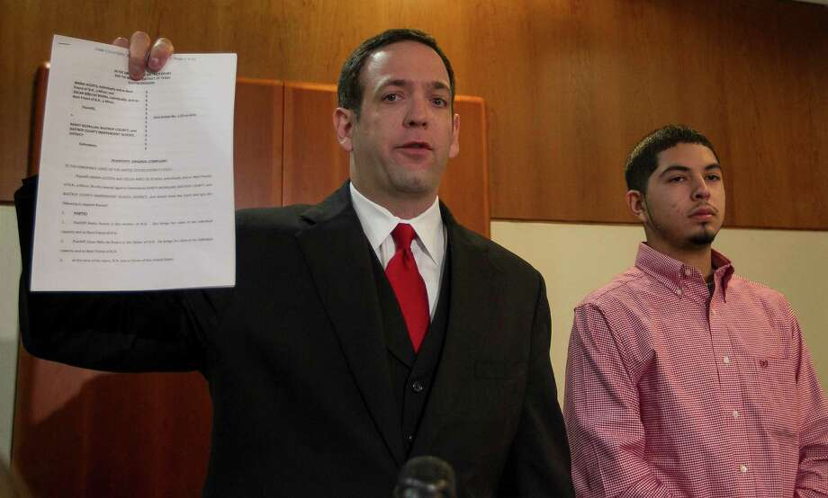 Attorney Adam Loewy, left,  holds up a copy of the lawsuit he has filed for the family of Noe Nino de Rivera, 17, as Noe's brother Jesus Nino de Rivera, right, looks on during a press conference in Austin on Nov. 26. Nino de Rivera was critically injured when he fell and hit his head after Bastrop County Deputy Randy McMillan used his Taser against the teen. The family  filed a lawsuit in federal court against Deputy McMillan, Bastrop County and Bastrop ISD.   (RODOLFO GONZALEZ / AMERICAN-STATESMAN ) Photo: Rodolfo Gonzalez