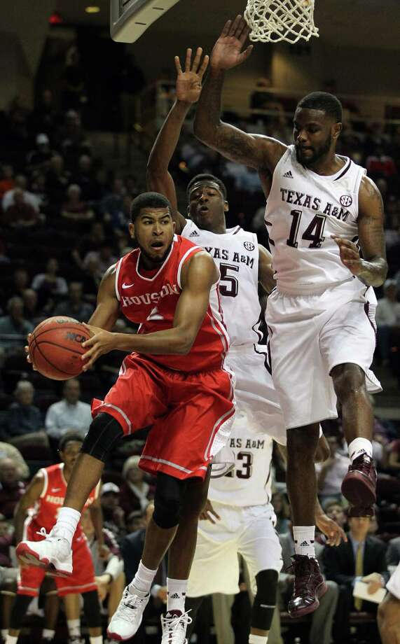 Houston's L.J. Rose. left, looks to pass as Texas A&M's Davonte Fitzgerals, center, and Kourtney Roberson defend during the first half of an NCAA college basketball game, Wednesday, December 3, 2013, at Reed Arena in College Station, TX. Photo: Eric Christian Smith, For The Chronicle