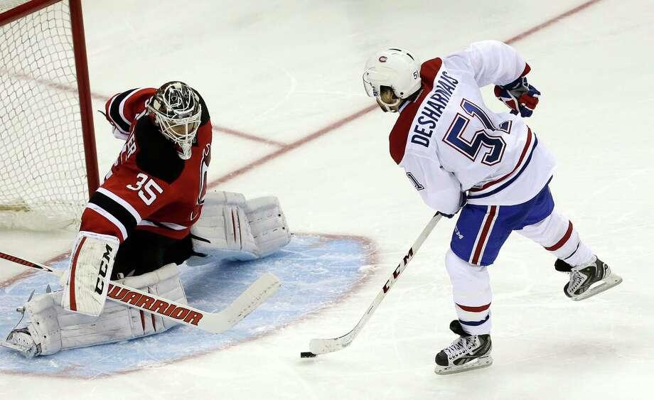 Montreal Canadiens center David Desharnais (51) skates against New Jersey Devils goalie Cory Schneider to score a goal in a shootout in an NHL hockey game, Wednesday, Dec. 4, 2013, in Newark, N.J. The Canadiens won 4-3. (AP Photo/Julio Cortez) ORG XMIT: NJJC114 Photo: Julio Cortez / AP