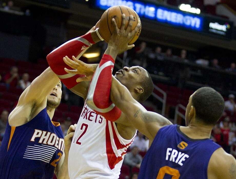 Rockets power forward Dwight Howard (12) goes up for a shot with Suns center Miles Plumlee (22) and Suns power forward Channing Frye (8) defending. Photo: Brett Coomer, Houston Chronicle