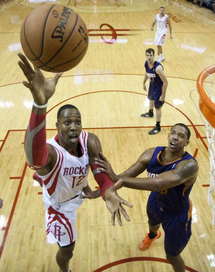 Rockets power forward Dwight Howard (12) goes up for a shot with Suns power forward Channing Frye (8) defending. Photo: Brett Coomer, Houston Chronicle