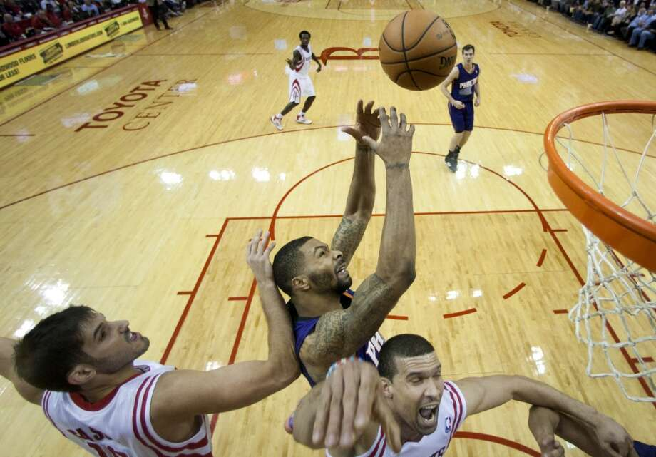 Suns power forward Markieff Morris, center, beats Rockets small forward Omri Casspi (18) and Rockets shooting guard Francisco Garcia (32) to a rebound. Photo: Brett Coomer, Houston Chronicle