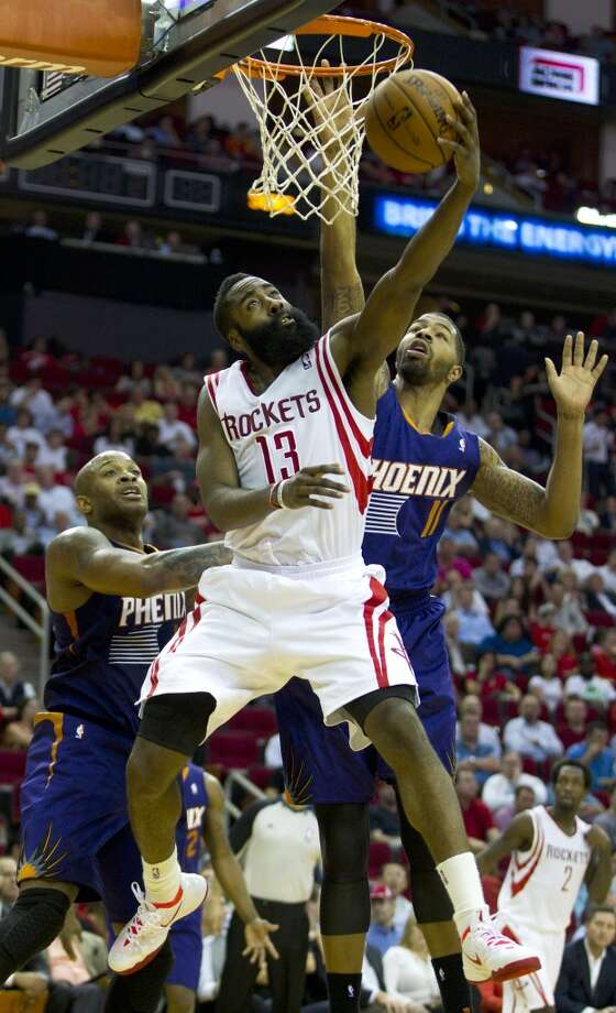 Rockets shooting guard James Harden (13) leaps past Suns power forward Markieff Morris (11) for a reverse layup. Photo: Brett Coomer, Houston Chronicle