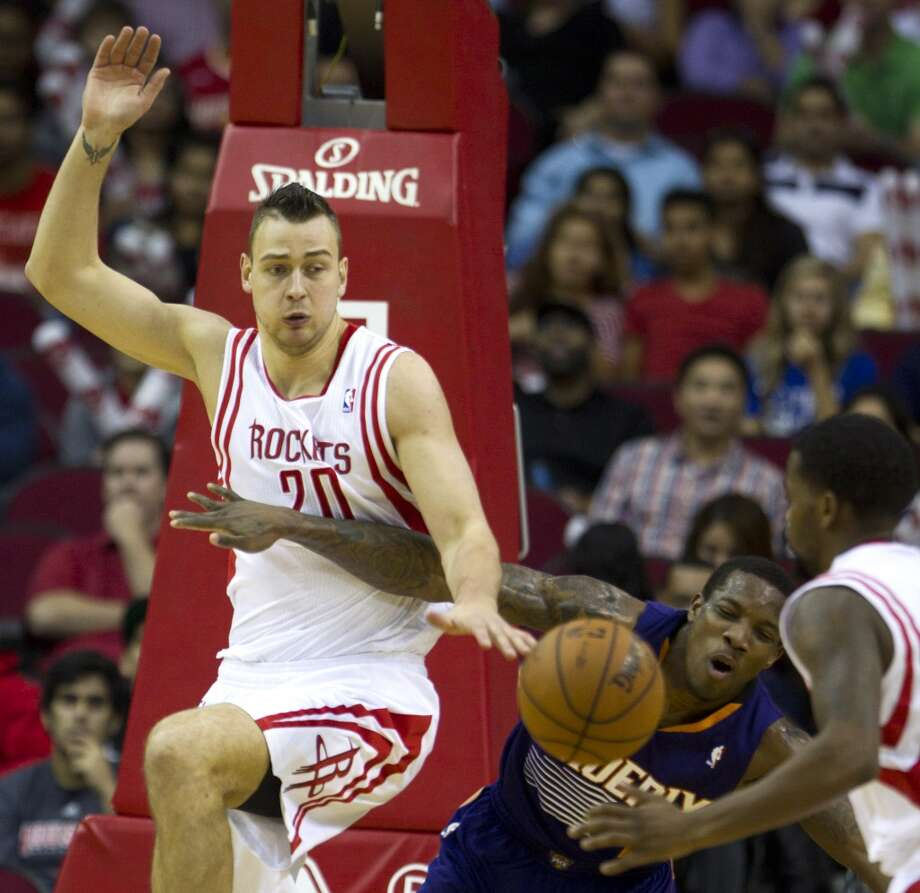Rockets power forward Donatas Motiejunas (20) and Suns point guard Eric Bledsoe (2) go after a loose ball. Photo: Brett Coomer, Houston Chronicle