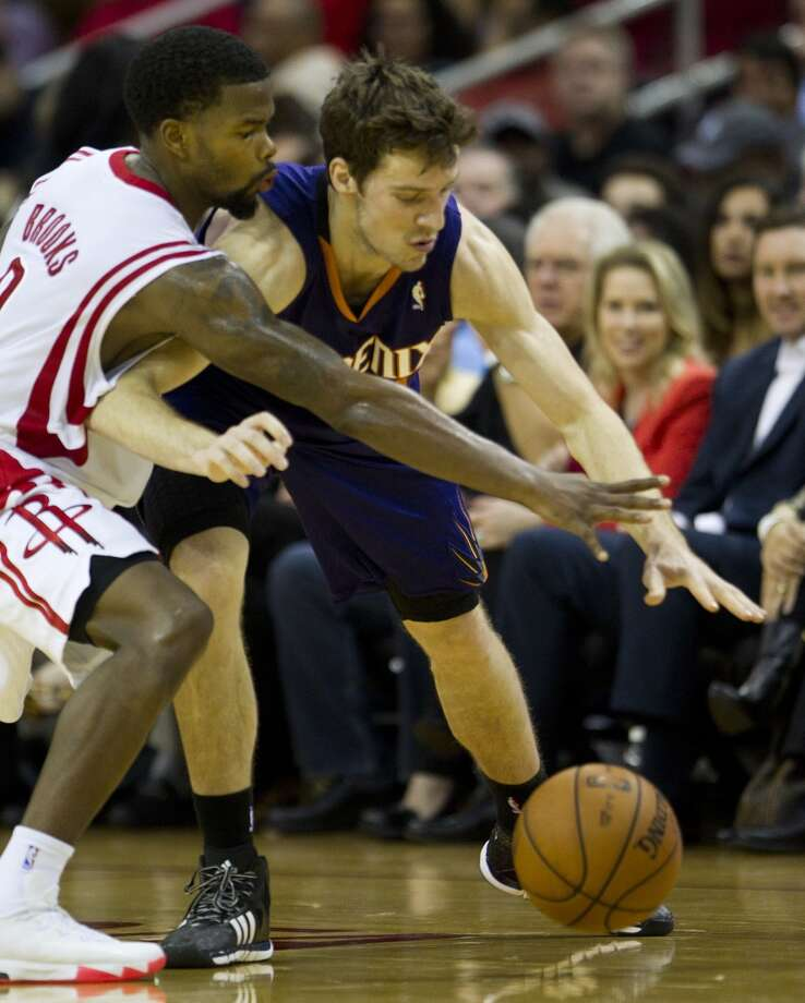 Rockets point guard Aaron Brooks (0) reaches in to try an steal a ball from Suns shooting guard Goran Dragic (1). Photo: Brett Coomer, Houston Chronicle