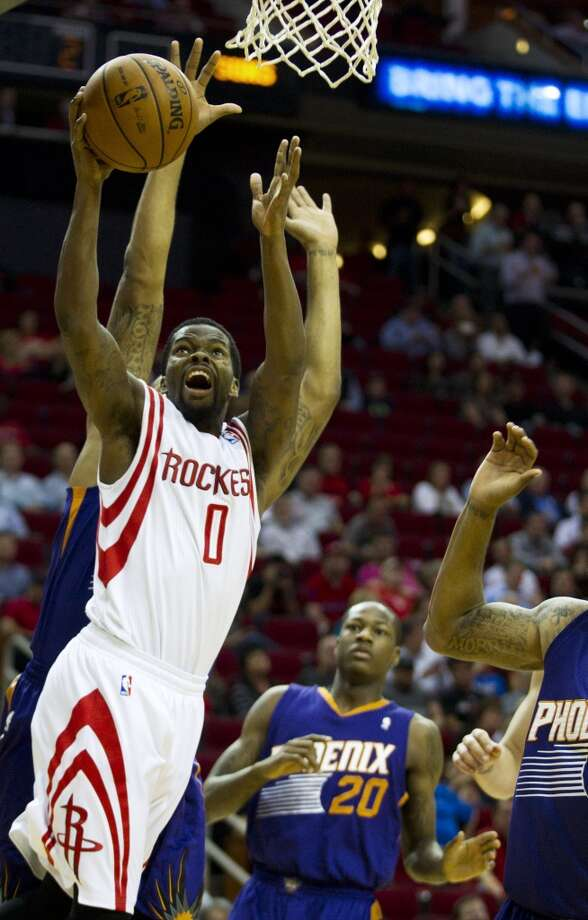 Rockets point guard Aaron Brooks (0) drives to the basket past Suns shooting guard Archie Goodwin (20). Photo: Brett Coomer, Houston Chronicle