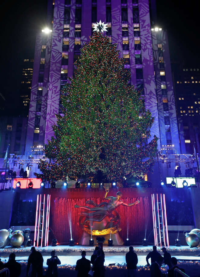 Workers linger in front of the Rockefeller Center Christmas tree after it was lit during a ceremony,Wednesday, Dec. 4, 2013, in New York. Some 45,000 energy efficient LED lights adorn the 76-foot tree. Photo: Kathy Willens, AP / Associated Press