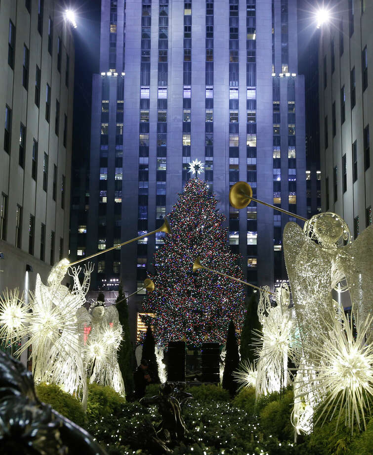The Rockefeller Center Christmas tree is shown surrounded by angels in a view from the Channel Gardens, Wednesday, Dec. 4, 2013, in New York.  Some 45,000 energy efficient LED lights adorn the 76-foot tree. Photo: Kathy Willens, AP / Associated Press