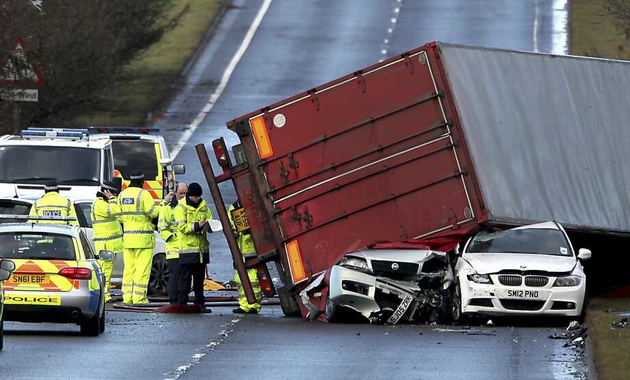 Toppled by high winds, a truck sits on top of two cars after a fatal accident near Bathgate, Scotland. Winds of 