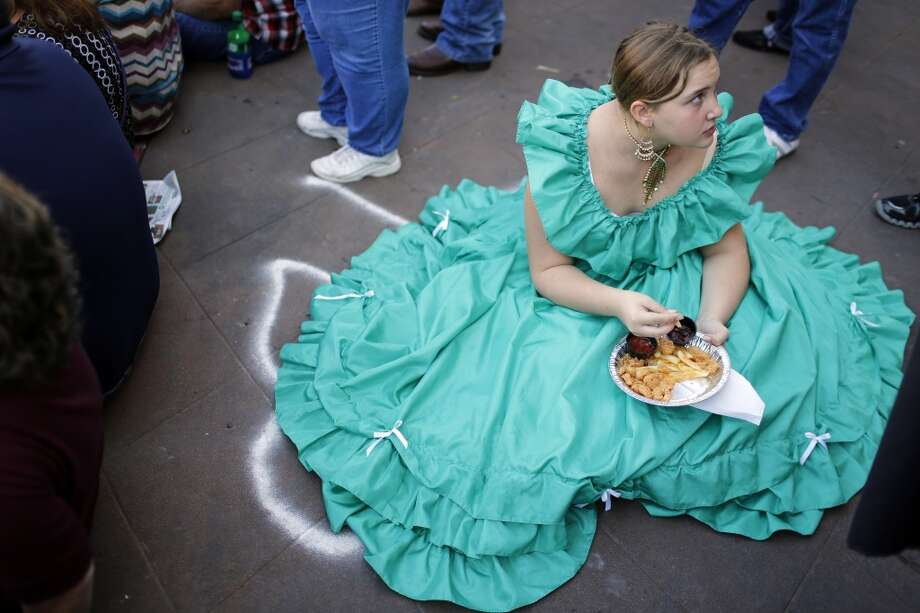 Elissa Oeschler of Cypress, takes a break to enjoy a friend shrimp platter, Saturday, December 1, 2012 during the annual Dickens on The Strand celebration in Galveston, Texas. (Todd Spoth / For The Chronicle) Photo: Houston Chronicle