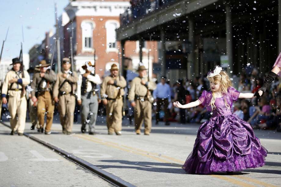 5-year-old Kailey Conner of Houston, attempts to catch a piece of falling faux snow while walking the parade route, Saturday, December 1, 2012 during the annual Dickens on The Strand celebration in Galveston, Texas. (Todd Spoth / For The Chronicle) Photo: Houston Chronicle