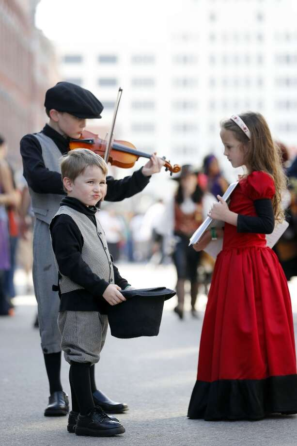 Travis Gibson, 9, rear left, plays the violin as sister, Mary Cathryn, 6, right, displays sheet music with brother, Peter, 4, front holds a hat for donations, Saturday, December 1, 2012 during the annual Dickens on The Strand celebration in Galveston, Texas. (Todd Spoth / For The Chronicle) Photo: Houston Chronicle