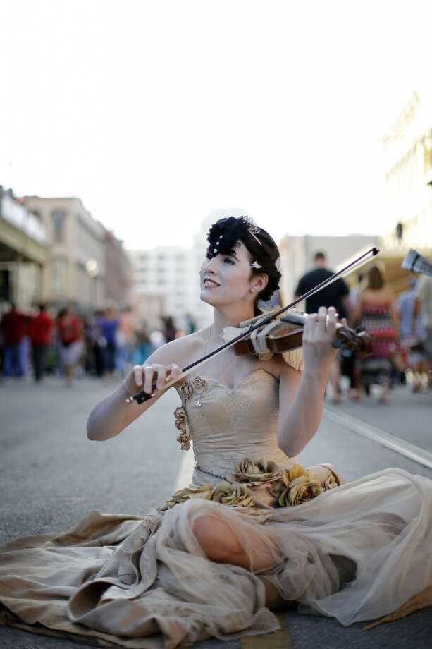 Gina Williamson, sits in the street and plays the violin for passersby, Saturday, December 1, 2012 during the annual Dickens on The Strand celebration in Galveston, Texas. (Todd Spoth / For The Chronicle) Photo: Houston Chronicle
