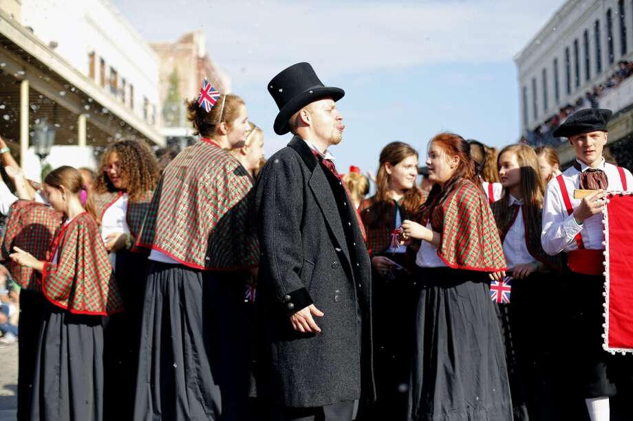 Members of the Katy junior high choir stop to revel in the falling faux snow, Saturday, December 1, 2012 during the annual Dickens on The Strand celebration in Galveston, Texas. (Todd Spoth / For The Chronicle) Photo: Houston Chronicle
