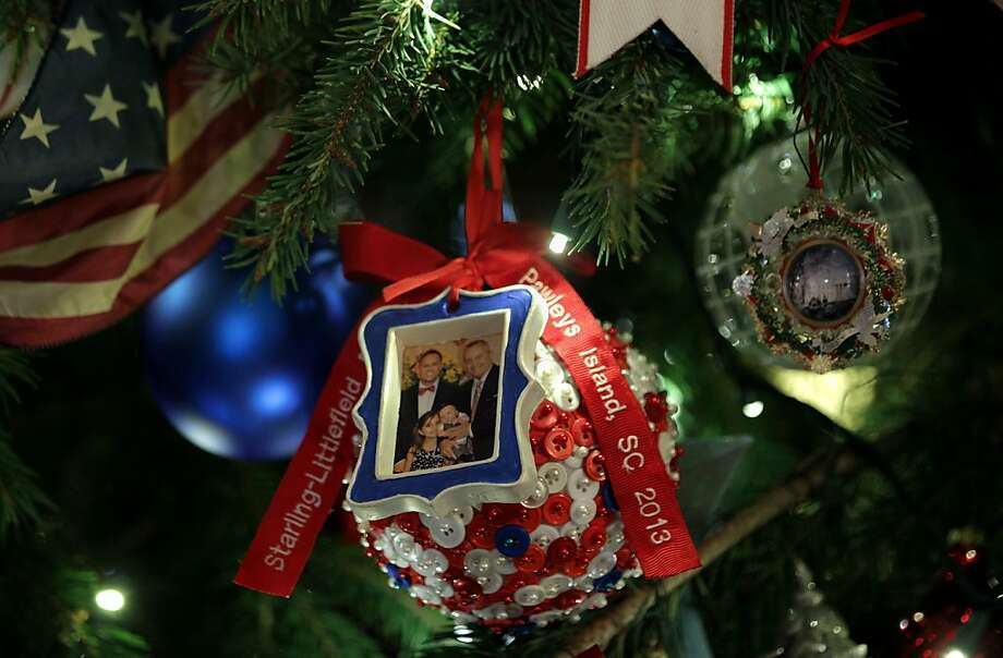 Ornaments hang on the official White House Christmas Tree in the Blue Room of the White House during an event to preview the 2013 holiday decorations December 4, 2013 in Washington, DC. U.S. first lady Michelle Obama hosted military families for the first viewing of the decorations and demonstrating holiday crafts and treats to military children. Photo: Alex Wong, Getty Images