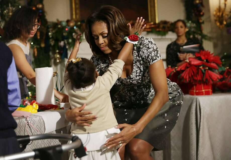 First lady Michelle Obama hugs a girl at the State Dining Room of the White House during an event to preview the 2013 holiday decorations December 4, 2013 in Washington, DC. The first lady hosted military families for the first viewing of the decorations and demonstrating holiday crafts and treats to military children. Photo: Alex Wong, Getty Images