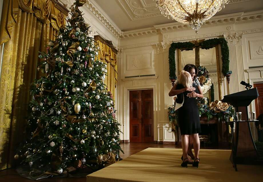 First lady Michelle Obama (right) hugs Diane Cole of Phoenix, Arizona, at the East Room of the White House during an event to preview the 2013 holiday decorations December 4, 2013 in Washington, DC. The first lady hosted military families for the first viewing of the decorations and demonstrating holiday crafts and treats to military children. Photo: Alex Wong, Getty Images