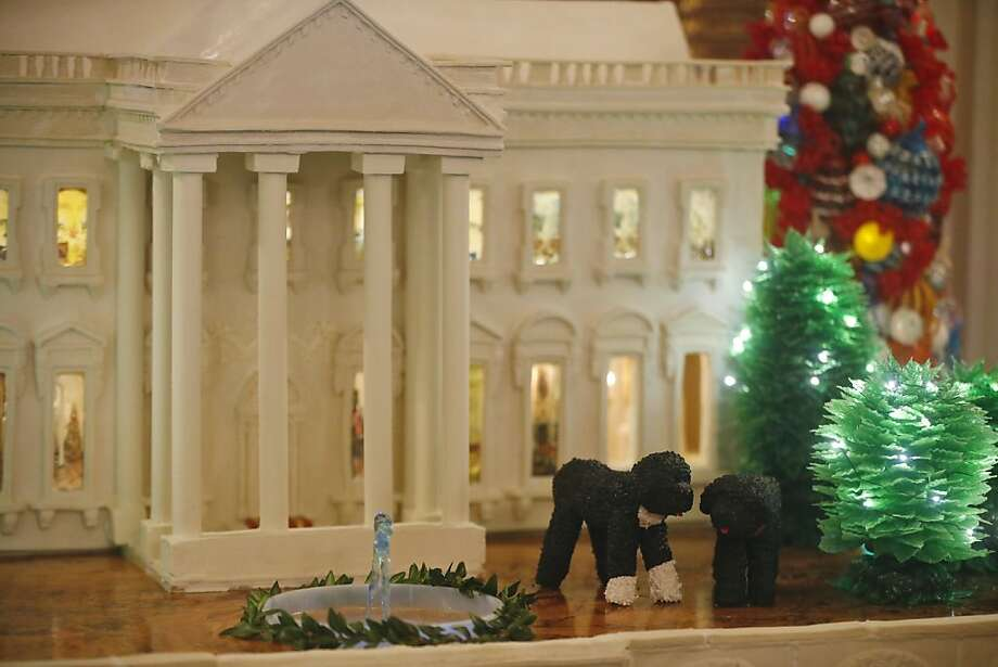 "The 300 pound gingerbread White House replica with a mini Bo and Sunny is displayed in the State Dining Room of the White House in Washington, Wednesday, Dec. 4, 2013, during a press preview of the 2013 Christmas decorations, which is themed ""Gather Around"".  Photo: Charles Dharapak, Associated Press"