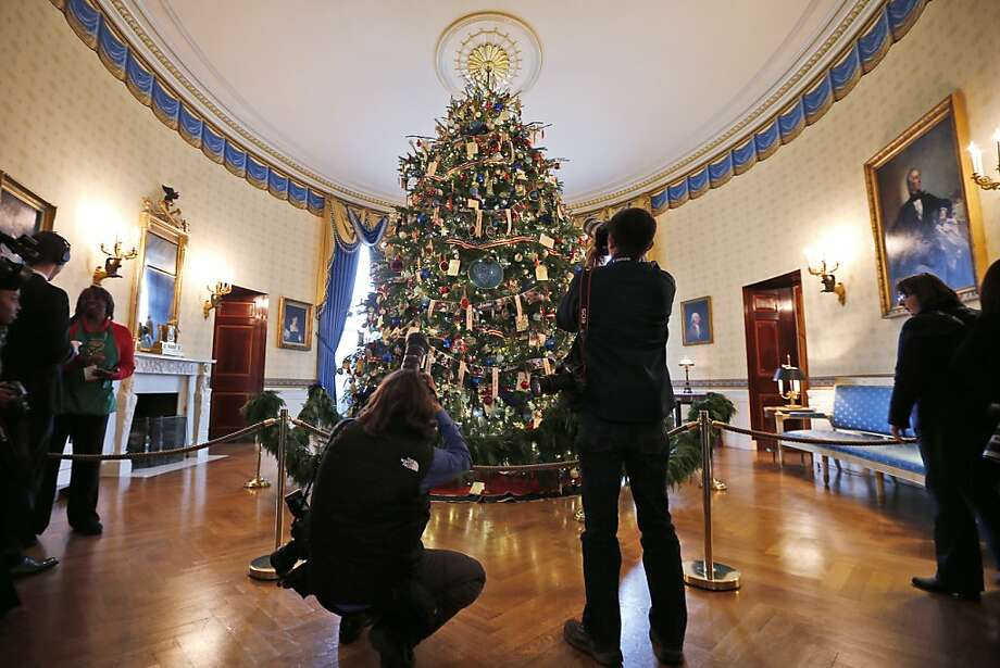 "Press photographers photograph the White House Christmas Tree in the Blue Room of the White House in Washington, Wednesday, Dec. 4, 2013, during a press preview of the 2013 Christmas decorations, which is themed ""Gather Around"". The 18.5 foot Douglas fir from Lehighton, Penn., features decorations honoring military families.  Photo: Charles Dharapak, Associated Press"