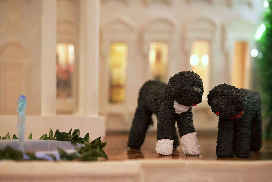 Figures of President Barack Obama's family dogs Bo, left, and Sunny, are seen in front of a gingerbread version of the White House, part of the holiday decorations in the State Dining Room of the White House in Washington, Wednesday, Dec. 4, 2013.  Photo: Jacquelyn Martin, Associated Press