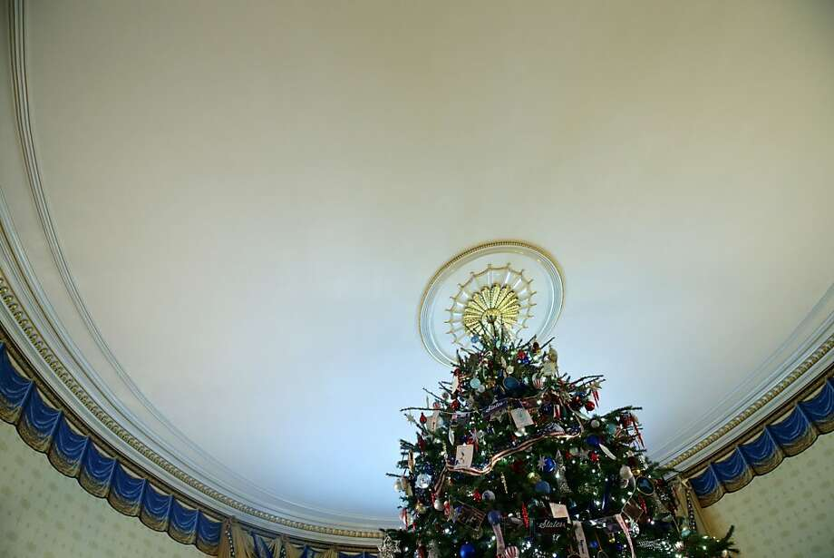 The official White House Christmas Tree stands in the Blue Room of the White House during an event to preview the 2013 holiday decorations December 4, 2013 in Washington, DC. U.S. first lady Michelle Obama hosted military families for the first viewing of the decorations and demonstrating holiday crafts and treats to military children. Photo: Alex Wong, Getty Images