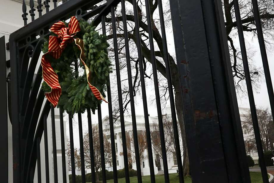 A Christmas wreath hangs on a gate of the White House December 4, 2013 in Washington, DC. U.S. first lady Michelle Obama will host military families for the first viewing of the 2013 holiday decorations and demonstrating holiday crafts and treats to military children. Photo: Alex Wong, Getty Images