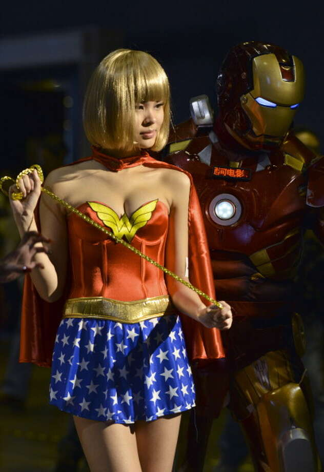 A Sony Playstation promotional girl dressed as Wonder Woman (L) poses for a picture next to Iron Man during the Asia Game Show (AGS) in Hong Kong on December 21, 2012. Photo: ANTONY DICKSON, AFP/Getty Images / 2012 AFP
