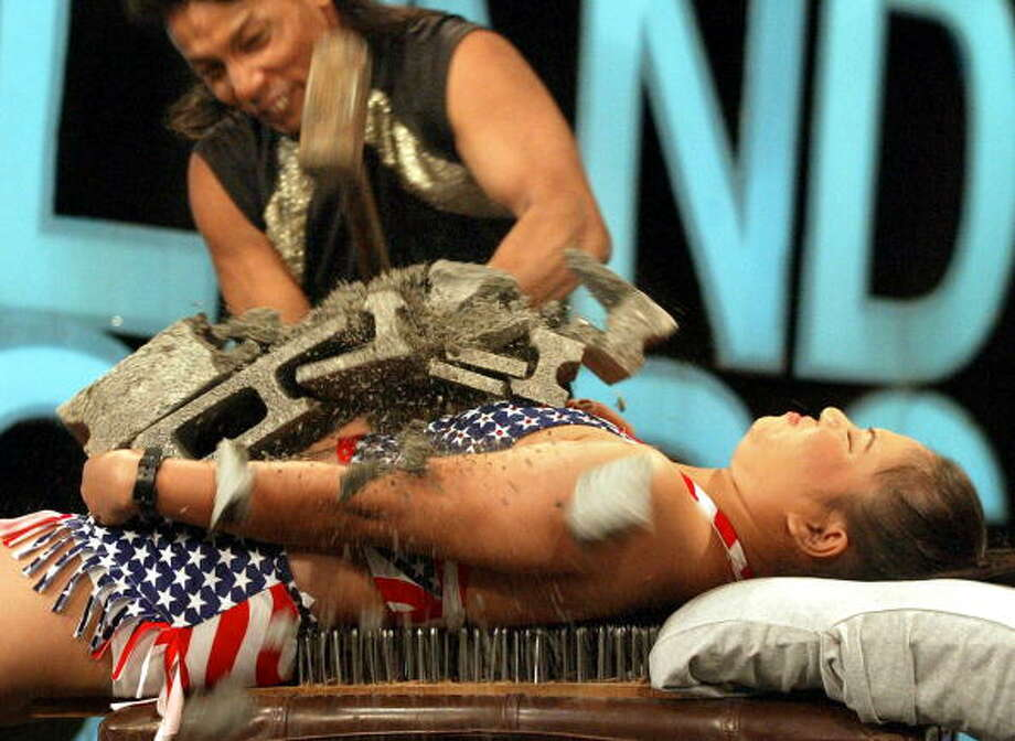 Self described wonder woman, Puangphaka Songsri, age 21, lies down on a bed of nails while her colleague breaks cinder-blocks on her chest at the set of a local television show in Bangkok, 02 September 2002. Photo: PORNCHAI KITTIWONGSAKUL, AFP/Getty Images / AFP