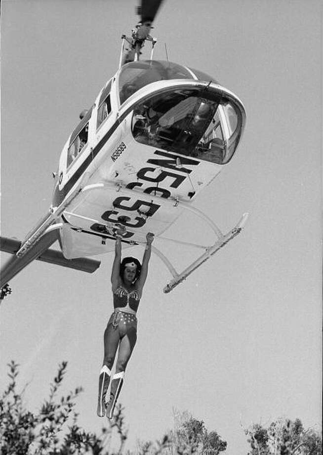 An unidentified stuntwoman, dressed as Wonder Woman, hangs from the landing struts of an airborne helicopter in an outtake from an episode from the television series 'The New Adventures of Wonder Woman' called 'Anschluss '77,' September 23, 1977. When the episode aired on television, the shot had been replaced with one where actress (and series star) Lynda Carter performed the stunt herself. Photo: CBS Photo Archive, Getty Images / 2005 CBS WORLDWIDE INC.