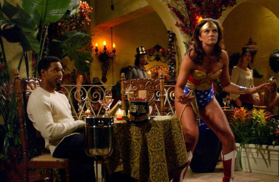 Full shot in restaurant of Jason George as J.T. sitting at table and looking at Misty May as Diana, who is wearing Wonder Woman costume. Photo: Monty Brinton, Warner Bros./Getty Images / Warner Bros.
