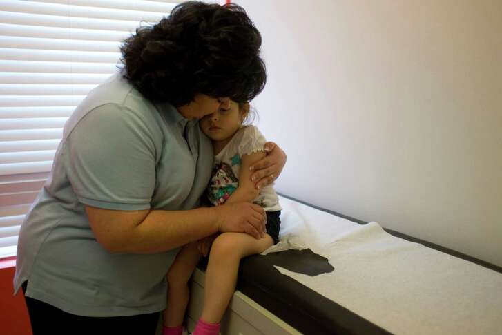 """Dina White, of Pearland, hugs her daughter Olivia White, 2, after it was determined she has the swine flu by a doctor at the Texas Children's Pediatric Associates in Pearland Thursday, Oct. 8, 2009.  """"It's just scary because it's not something that we are use to,"""" White said of her daughter getting the swine flu. """"It makes you worried especially with your own child."""" Dr. Matthew Wilber with the Texas Children's Pediatric Associates said typically this time of year he would see about 120 patients a week. However for the past three weeks he has seen about 145 patients where he has diagnosed about 50 a week with the swine flu. """"The most dramatic thing for me with this flu is not how sick the kids are getting, but the volume and sheer numbers,"""" Wilber said.  Wilber said though they can't directly test everyone's flu type, given the facts they are getting from hospitals and because of the time of year, the type of flu people are getting at this time is the swine flu. ( Johnny Hanson / Chronicle )"""