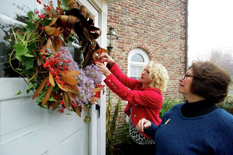 Denise Mangano, left, and Diane White, right, hang a second place ribbon on Jane Waugh's wreath, which placed in the Nature's Wonder category during the Shippan Garden Club's Doors of Shippan judging on Thursday, December 5, 2013. Photo: Lindsay Perry / Stamford Advocate