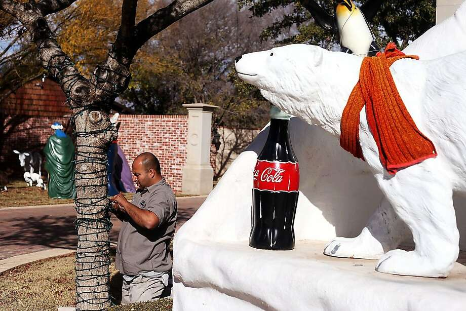 Nothing says Christmas like an plastic liter of Coke:Jesse Morales decorates a tree in the front-yard   Christmas display of his employer's home in Odessa, Texas. Photo: Edyta Blaszczyk, Associated Press