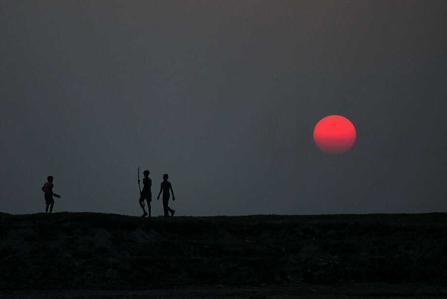 Kite collectors: Indian youths wait on mudflats near the River Ganges to scavenge kites whose tethers have been severed during kite-fighting competitions in Allahabad. Photo: Sanjay Kanojia, AFP/Getty Images