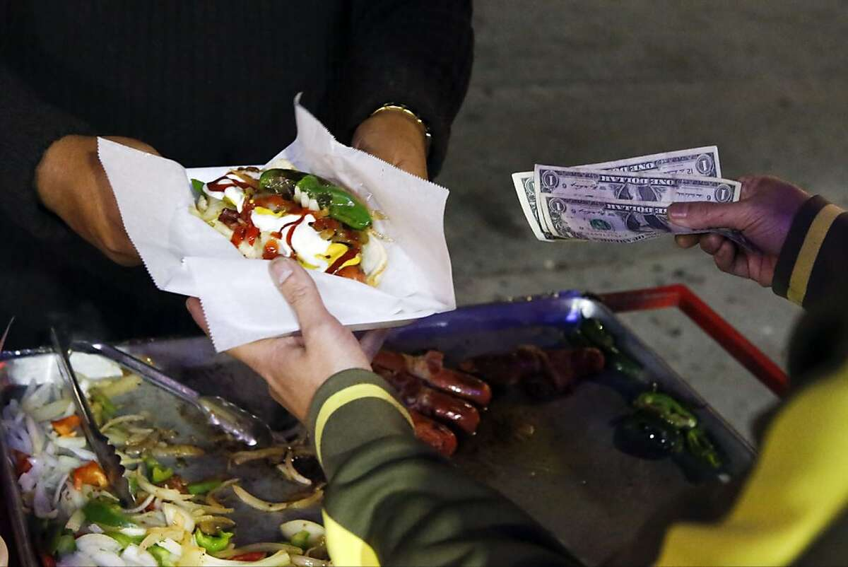 Carlos Dzul sells bacon-wrapped hot dogs on Sunset Boulevard in the Echo Park neighborhood of Los Angeles, Nov. 9, 2013. A plan introduced in the City Council would legalize and regulate street food vendors in Los Angeles, where decades of police crackdowns have failed to curb the enormous black market. (Patrick T. Fallon/The New York Times)